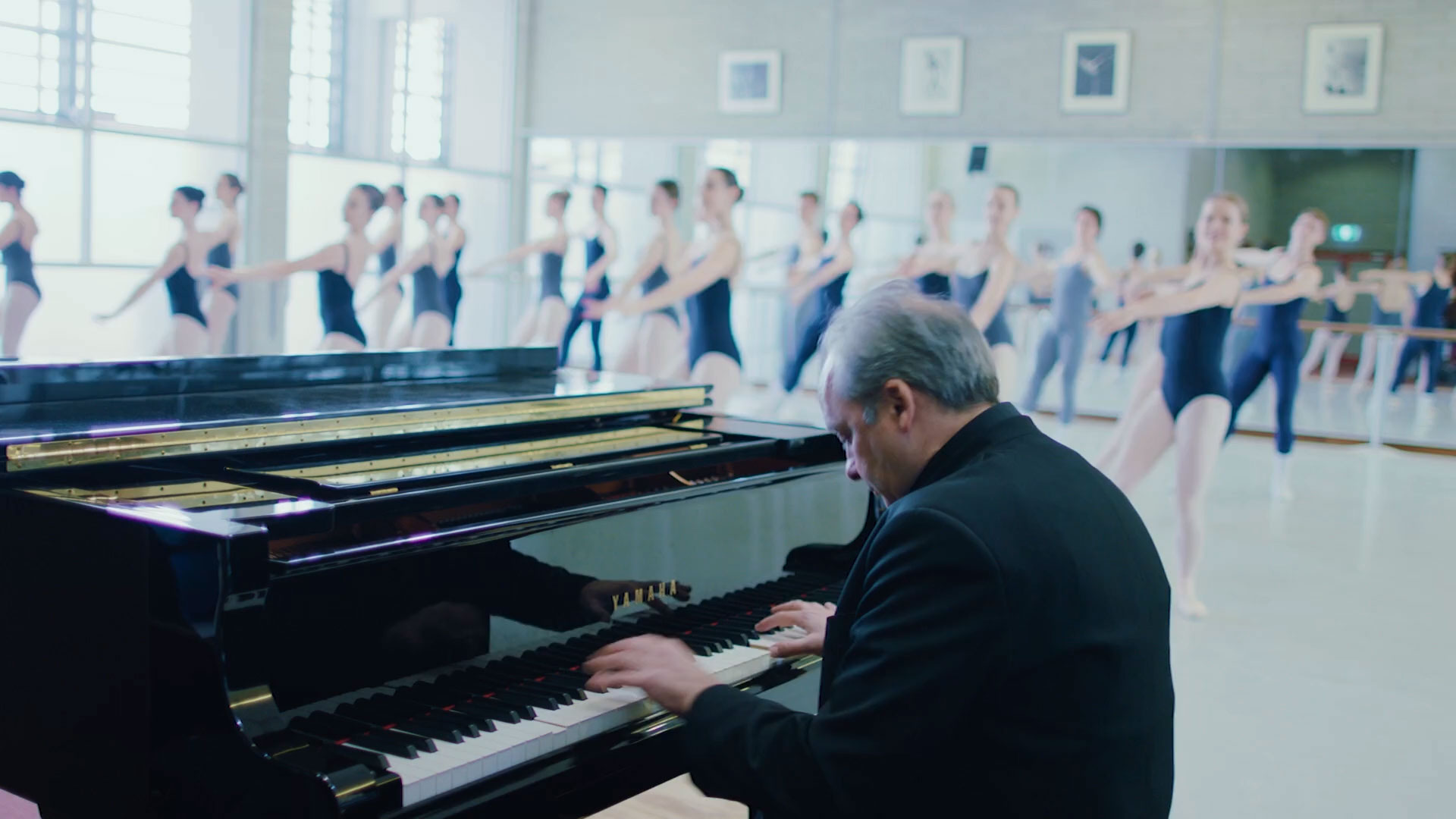Man playing piano with ballet dancers performing