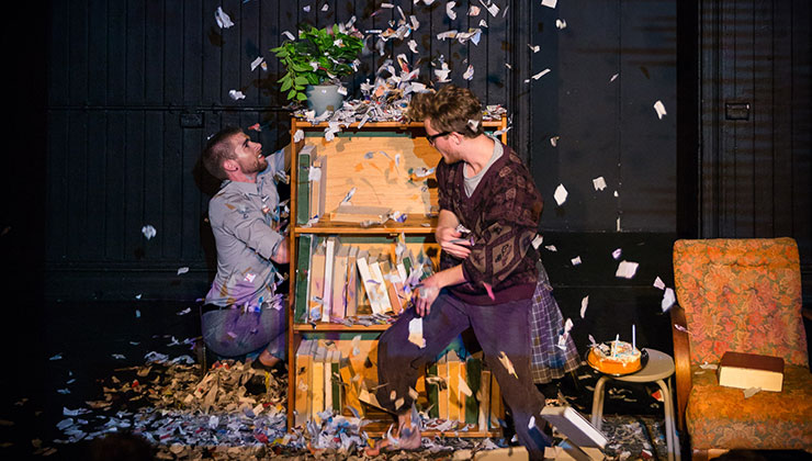 Two men throw torn paper into the air in a stage production